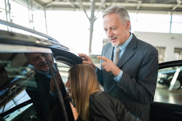 Frau, die mit dem verkäufer spricht, um ihr neues auto in einem modernen ausstellungsraum zu kaufen