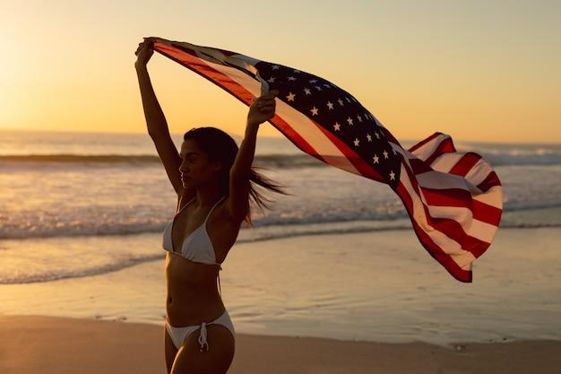 Frau, die mit dem wellenartig bewegen der amerikanischen flagge auf dem strand steht