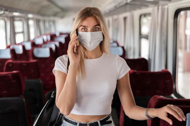 Frau, die mit dem zug reist und telefoniert, während sie eine medizinische maske trägt