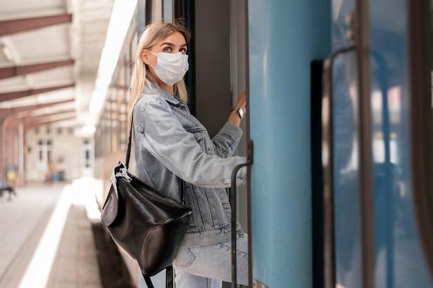 Frau, die mit dem zug reist und zum schutz eine medizinische maske trägt