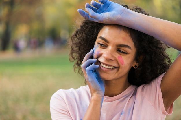 Frau, die mit den händen bedeckt im blauen pulver lächelt