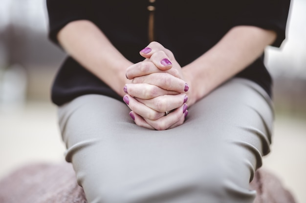 Frau, die mit den händen zusammen auf schoß sitzt, während sie betet