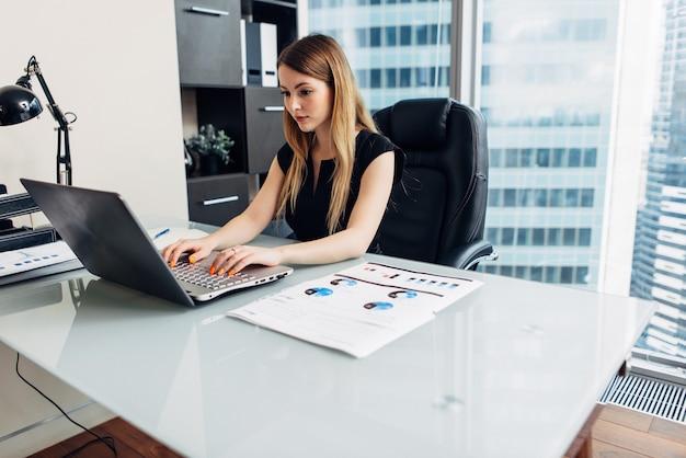 Frau, die mit dokumenten arbeitet, die am schreibtisch im büro sitzen.