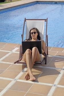 Frau, die mit einem computer im pool arbeitet