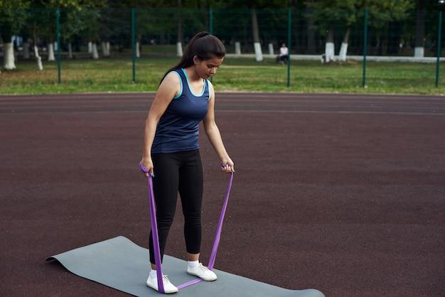 Frau, die mit einem elastischen fitnessband ausarbeitet