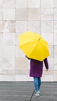 Frau, die mit einem gelben regenschirm auf einem steinarchitekturhintergrund geht.
