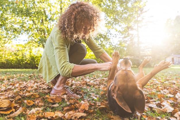 Frau, die mit einem hund im garten spielt