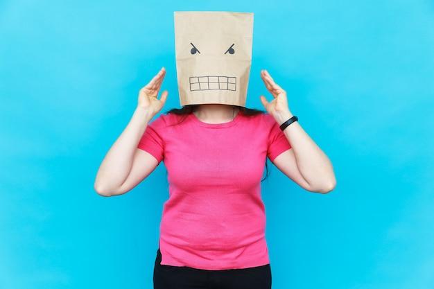 Frau, die mit einem karton auf ihrem kopf mit wütendem gesicht steht. emotionskonzept.