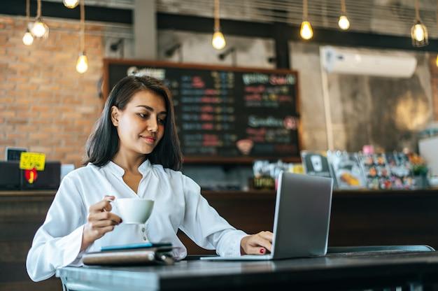 Frau, die mit einem laptop in einer kaffeestube sitzt und arbeitet