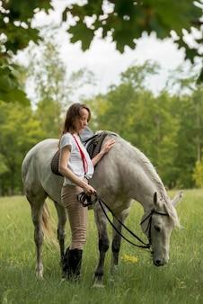 Frau, die mit einem pferd in der landschaft geht