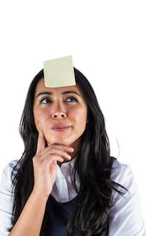 Frau, die mit einem post-it auf ihrem kopf denkt