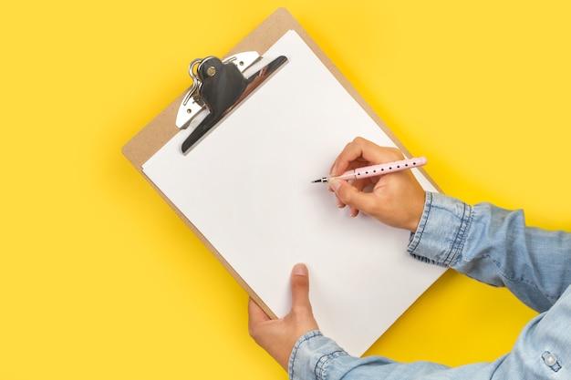 Frau, die mit einem rollenstift auf einer zwischenablage auf einem gelben hintergrund schreibt