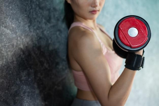 Frau, die mit einem roten dummkopf in der turnhalle trainierend steht.