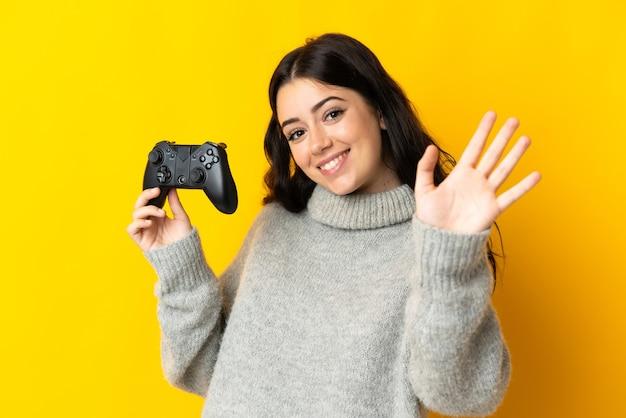 Frau, die mit einem videospielcontroller spielt, der auf gelbem hintergrund mit hand mit glücklichem ausdruck salutiert
