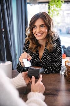 Frau, die mit einer debitkarte in einem restaurant zahlt, kellnerin, die ein zahlungsterminal hält