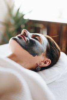 Frau, die mit einer gesichtsmaske am badekurort sich entspannt