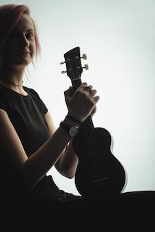Frau, die mit einer gitarre in der musikschule sitzt