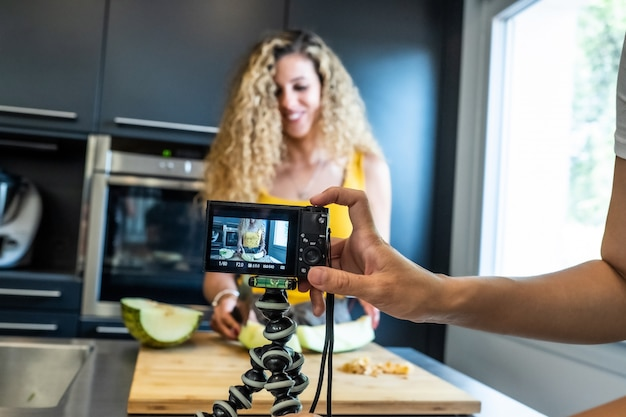Frau, die mit einer kamera wie einem melonenschneider in einer küche aufzeichnet