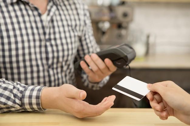 Frau, die mit einer kreditkarte am café zahlt