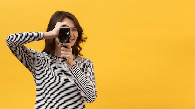 Frau, die mit einer retro-kamera mit kopienraum filmt