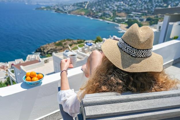 Frau, die mit einer tasse kaffee auf balkon entspannt
