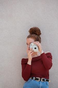 Frau, die mit einer weinlesekamera aufwirft