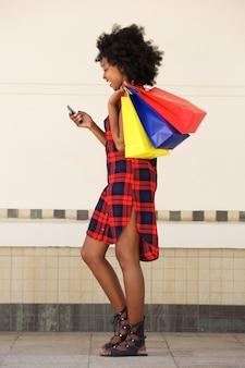 Frau, die mit einkaufstaschen und handy geht