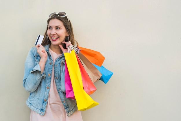 Frau, die mit einkaufstaschen und kreditkarte an der hellen wand steht