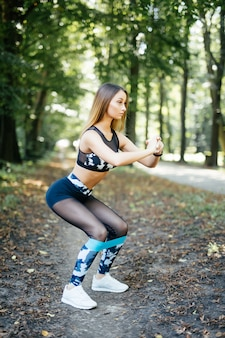 Frau, die mit elastischem widerstandsband im park trainiert