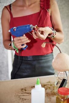 Frau, die mit elektrischer klebepistole arbeitet