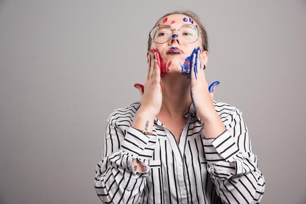 Frau, die mit farben auf ihrem gesicht auf grauem hintergrund aufwirft. hochwertiges foto