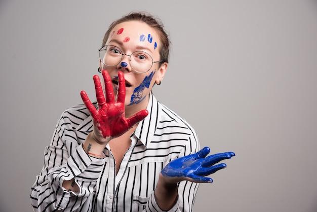 Frau, die mit farben auf ihrem gesicht auf grauem hintergrund aufwirft.