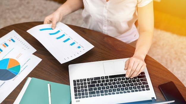 Frau, die mit finanzdiagrammen auf dem tisch arbeitet. laptop, papiere
