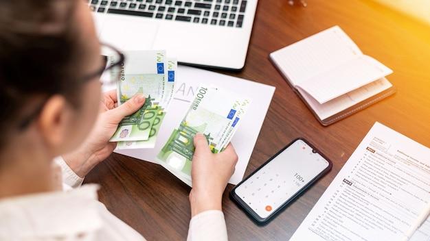 Frau, die mit finanzen arbeitet, die geld auf dem tisch zählen. smertphone, notizblock