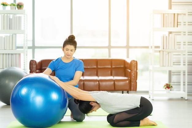 Frau, die mit fitnessball der sportlerinnen arbeitet, die yoga praktizieren. stretching mit fitnessball zu hause