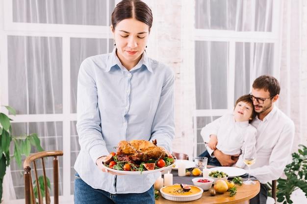 Frau, die mit gebackenem huhn in der platte steht
