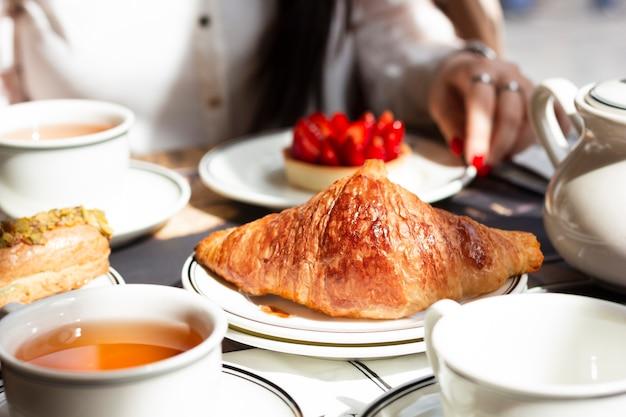 Frau, die mit gebäckzusammenstellung frühstückt