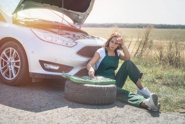 Frau, die mit gebrochenem rad ihres autos arbeitet und auf hilfe wartet