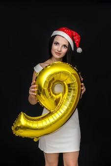 Frau, die mit goldenem luftballon aufwirft