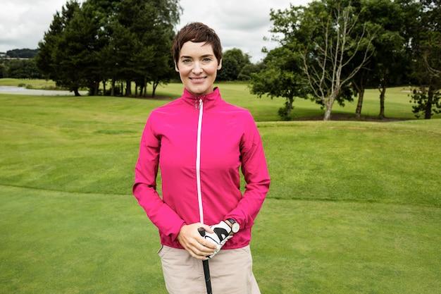 Frau, die mit golfschläger im golfplatz steht