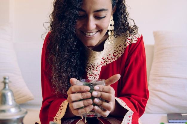 Frau, die mit händen grünen arabischen tee hält