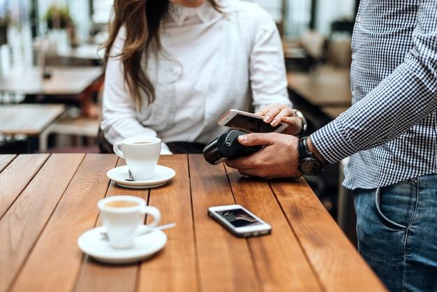 Frau, die mit handy im caférestaurant zahlt.
