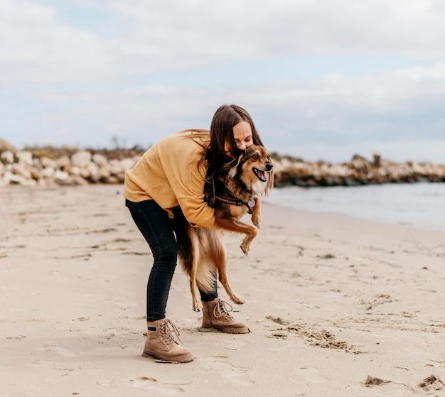 Frau, die mit hund am strand spielt