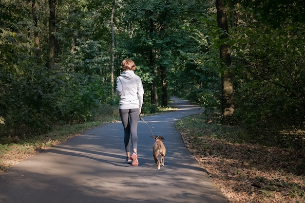 Frau, die mit hund im schönen wald joggt. junge weibliche person mit haustier, das überlauflaufübung in frischer luft tut.