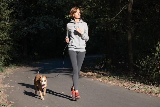 Frau, die mit hund in einem park joggt. junge weibliche person mit haustier, das laufübung im wald tut