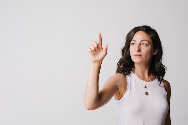 Frau, die mit ihrem finger einen bildschirm berührt