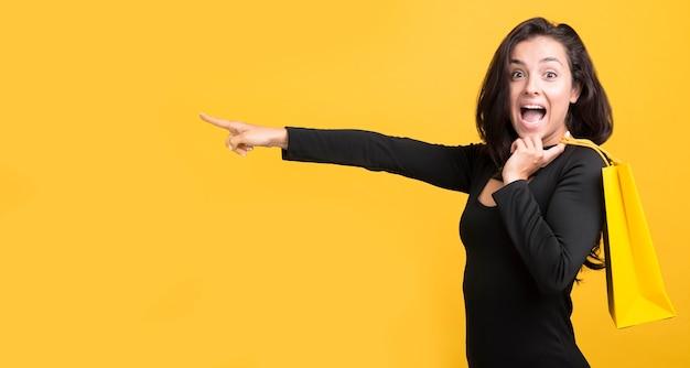 Frau, die mit ihrem finger schwarzen freitag-einkaufsereignis zeigt