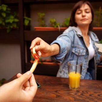 Frau, die mit ihrem freund mit pommes frites mit ketchup röstet