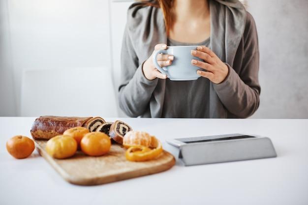 Frau, die mit ihrem freund zu mittag isst, klatscht und plaudert. gewöhnliche schlanke frau, die kaffee trinkt, clip über digitales tablett sieht und saftige mandarinen mit kuchen isst