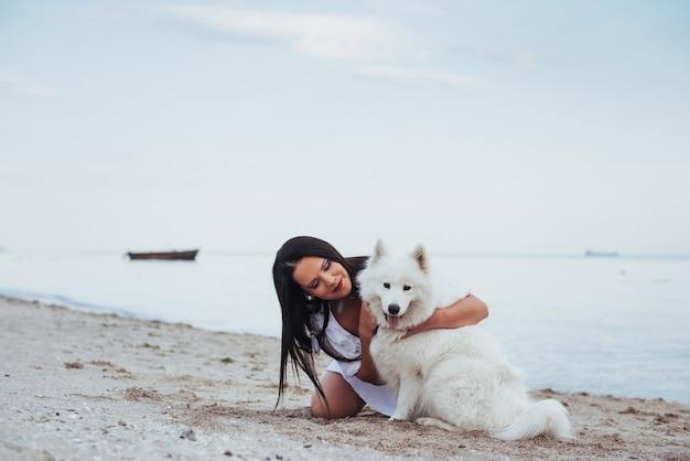 Frau, die mit ihrem hund am strand spielt